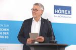 Vorstand Mario Werndl vor Wand mit HÖREX Logo
