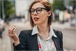 Frau mit Brille und Im-Ohr-Hörgerät unterwegs in der Stadt