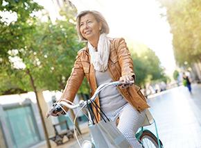 Ältere Dame auf einem Fahrrad in Stadt